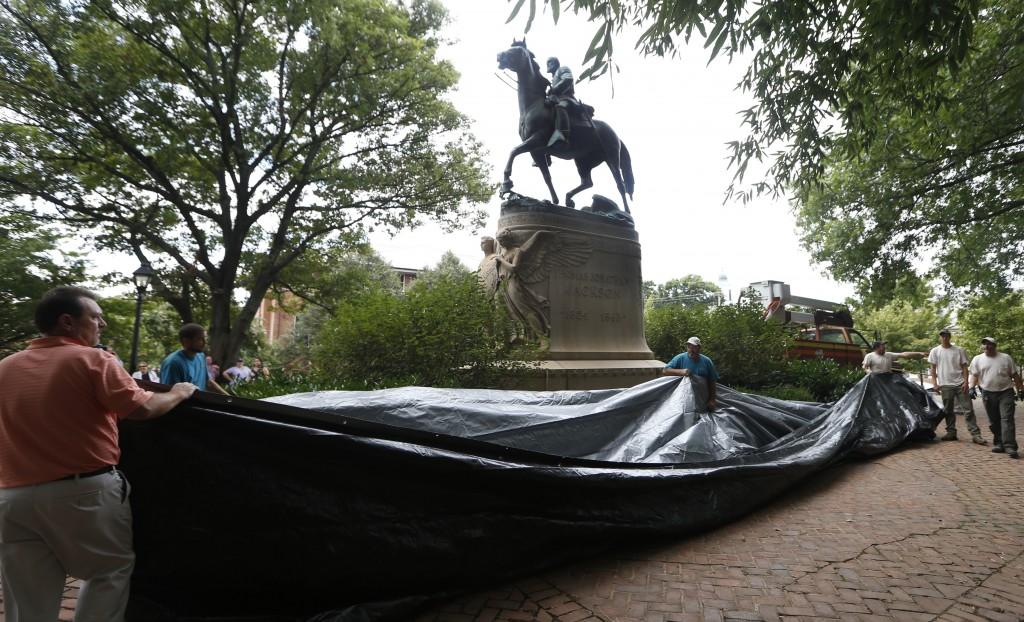 FILE - In this Aug. 23, 2017, file photo, city workers prepare to drape a tarp over the statue of Confederate General Stonewall Jackson in Justice par
