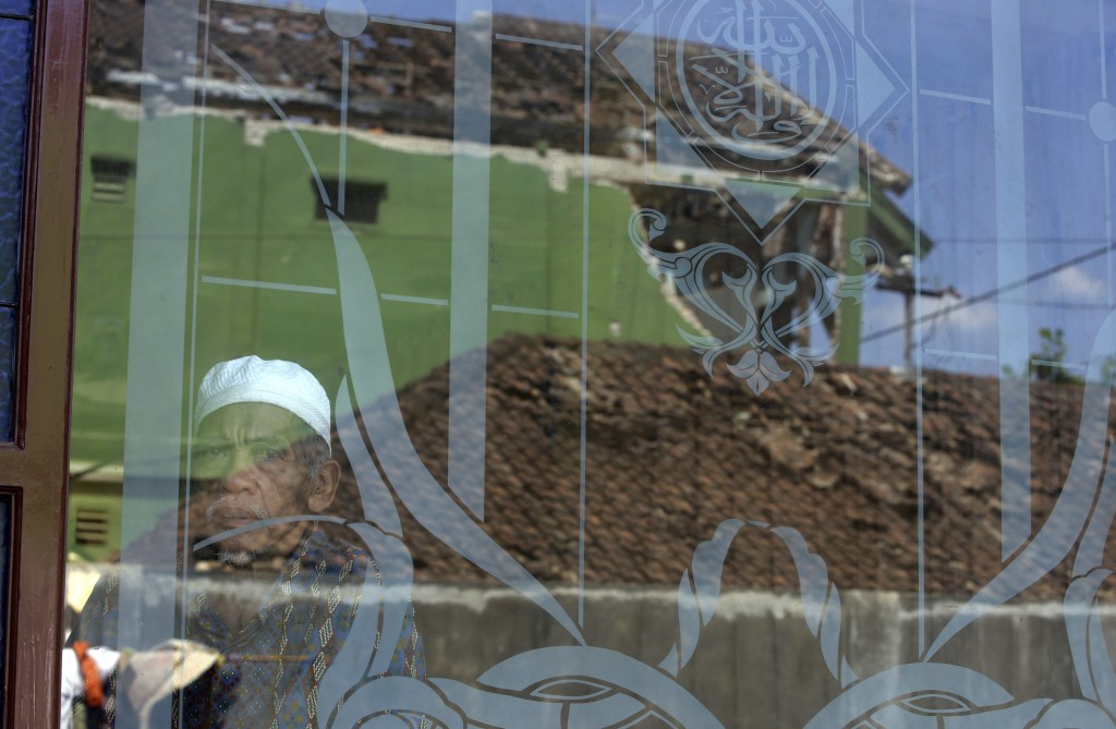 A man looks out from a mosque window as damaged homes are reflected on a glass window in the Kekait village affected by Sunday's earthquake in North L