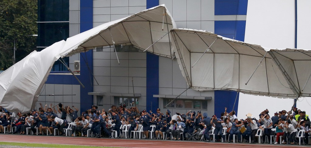 In this Wednesday, Aug. 8, 2018, file photo, Philippine National Police officers and employees react as their tent is toppled by a hovering police hel