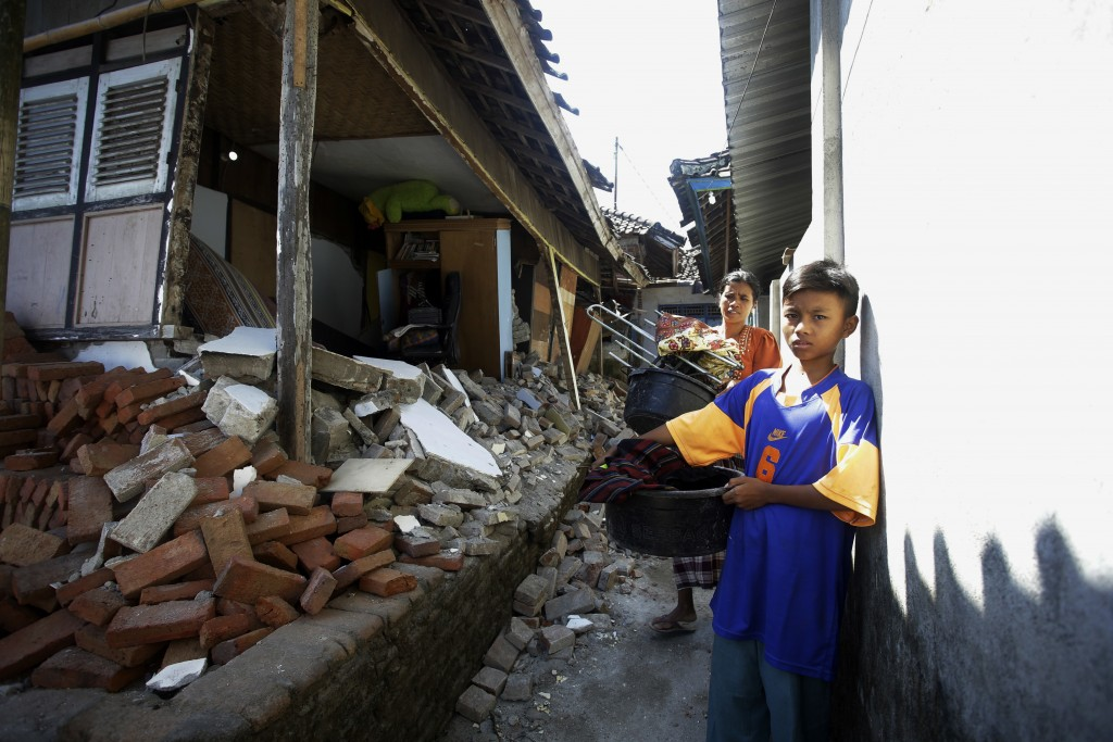 Villagers carry buckets pass a damaged house at Kekait village affected by Sunday's earthquake in North Lombok, Indonesia, Wednesday, Aug. 8, 2018. Ai...