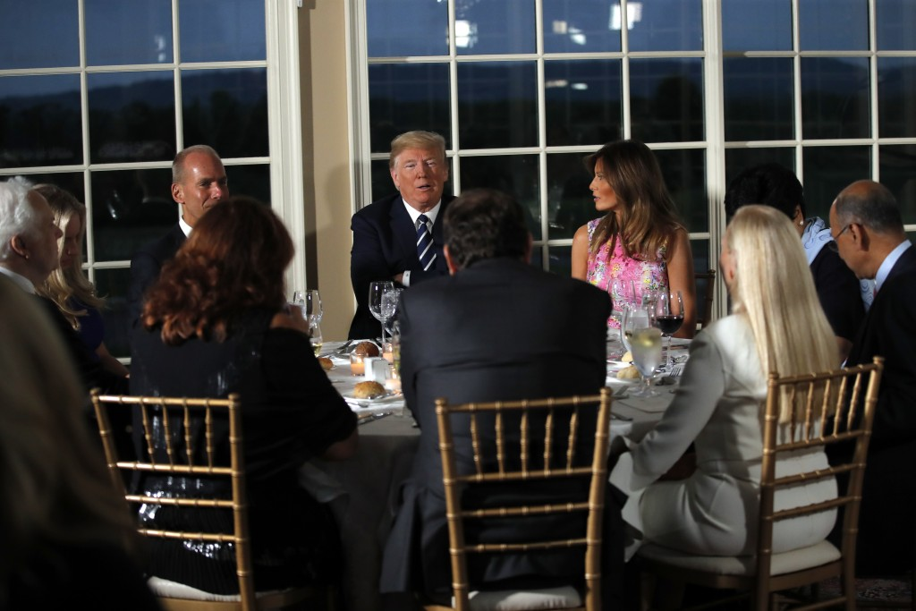President Donald Trump sits with first lady Melania Trump as he meets with business leaders, Tuesday, Aug. 7, 2018, at Trump National Golf Club in Bed