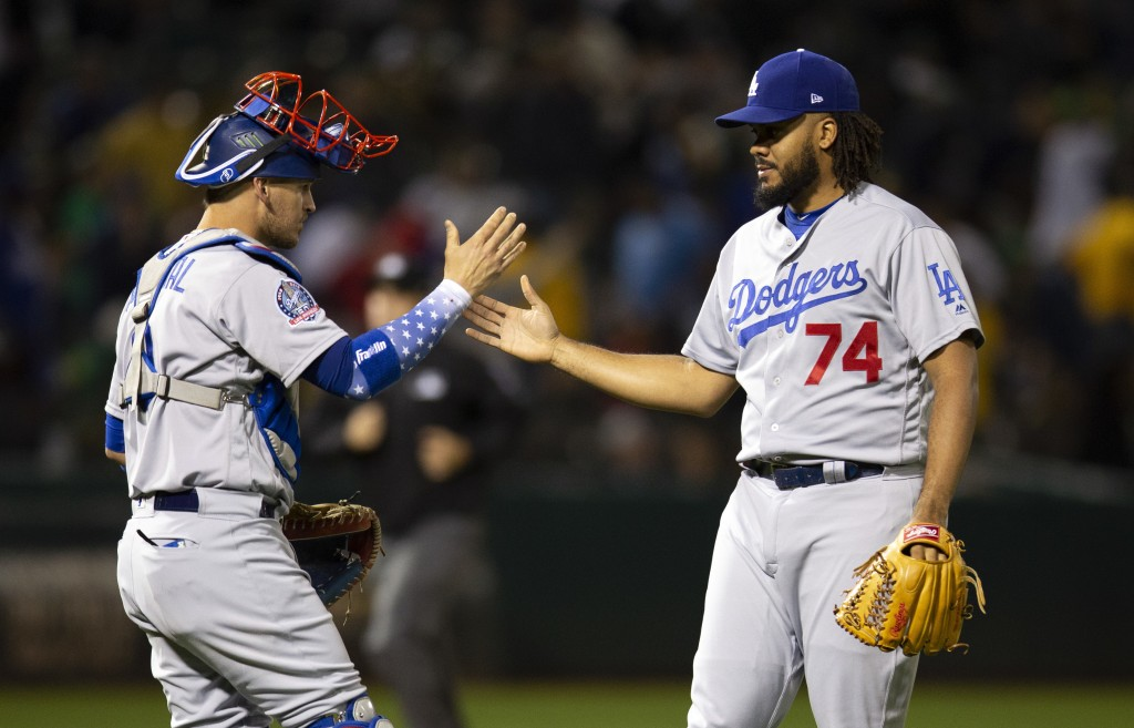 Los Angeles Dodgers catcher Yasmani Grandal (9) and pitcher Kenley Jansen (74) celebrate the team's 4-2 victory over the Oakland Athletics in a baseba