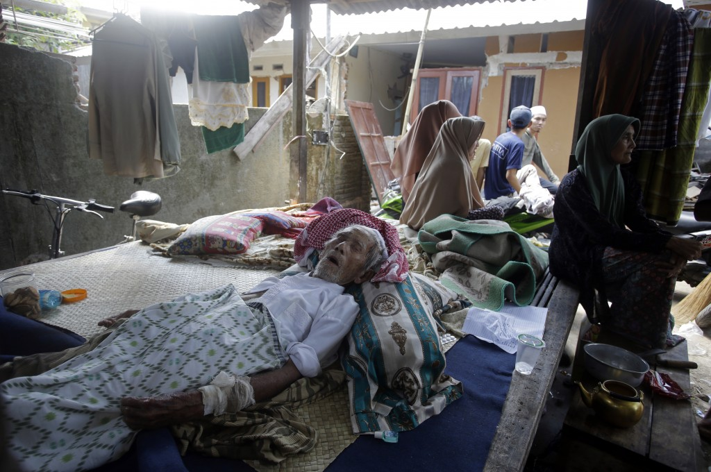 An elderly man injured in an earthquake lies at a temporary shelter in the Kekait village affected by Sunday's earthquake in North Lombok, Indonesia, ...
