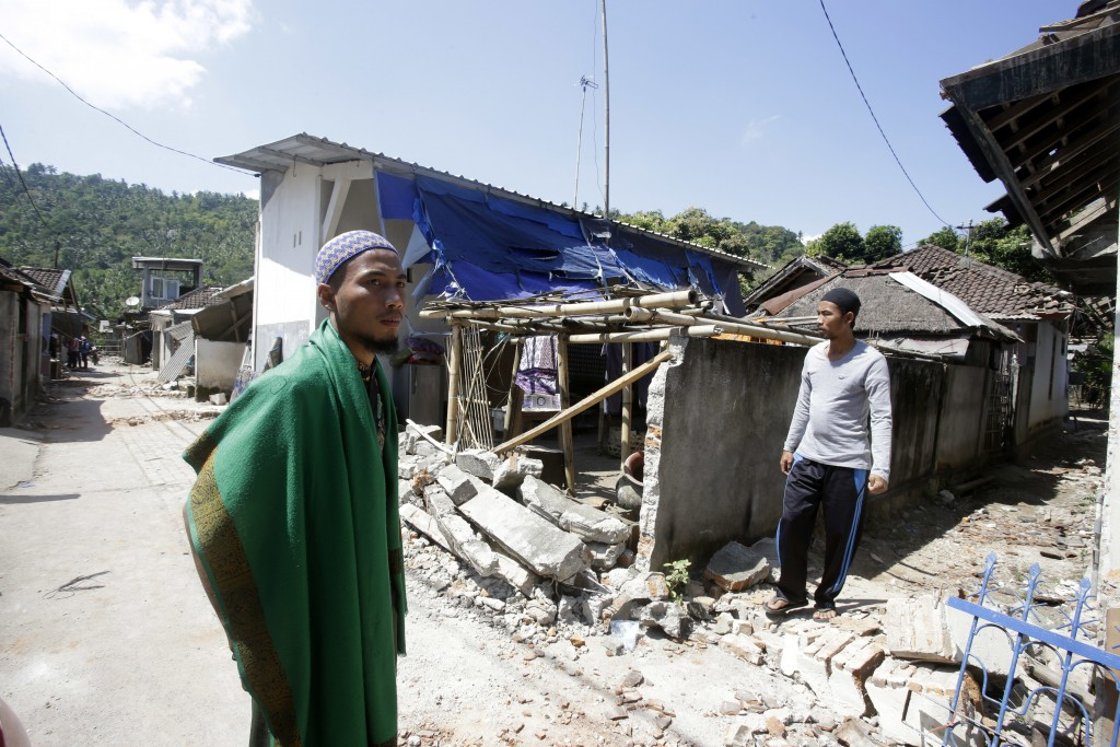 Villagers visit their destroyed home in the Kekait village affected by Sunday's earthquake in North Lombok, Indonesia, Wednesday, Aug. 8, 2018. Aid ha...