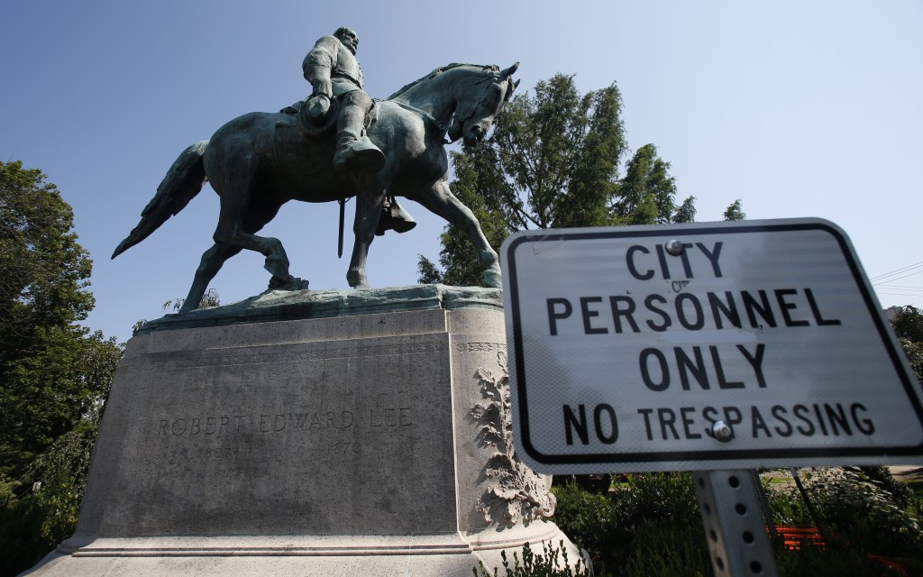 In this Monday, Aug. 6, 2018 photo, a No Trespassing sign is displayed in front of a statue of Robert E. Lee in Charlottesville, Va., at the park that