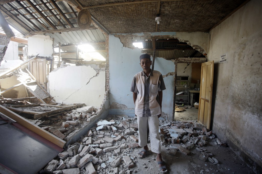Mohammad Muzak inspects his damaged home in the Kekait village affected by Sunday's earthquake in North Lombok, Indonesia, Wednesday, Aug. 8, 2018. Ai