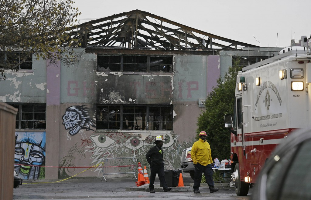 FILE - In this Dec. 7, 2016 file photo, Oakland fire officials walk past the remains of the Ghost Ship warehouse damaged from a deadly fire in Oakland