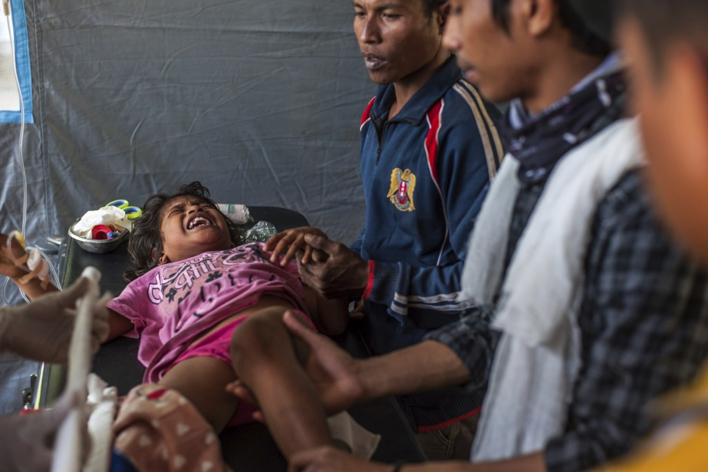 An Indonesian girl who was injured in Sunday's earthquake screams in pain as she is being treated at a makeshift hospital in Kayangan, North Lombok, I