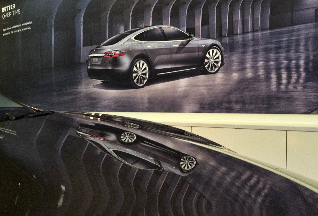An image of a Tesla model X is seen reflected on the hood of a new model 3 in the Tesla showroom in Santa Monica Calif. on Wednesday Aug. 8 2018