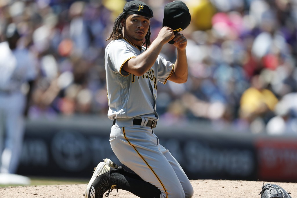 Pittsburgh Pirates starting pitcher Chris Archer puts on his cap after losing his balance while trying to field a single hit up the box by Colorado Ro...