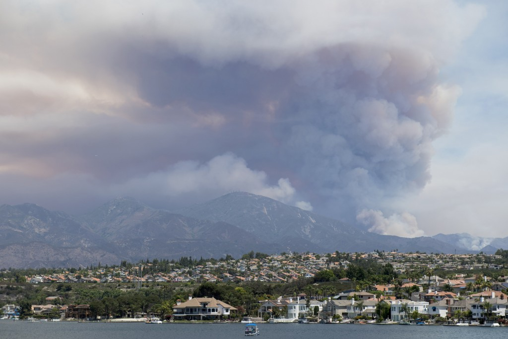 "A boat floats on Lake Mission Viejo as the ""Holy Fire"" burns in the mountains behind Mission Viejo, Calif., on Wednesday, Aug. 8, 2018. (Kevin Sulliva"