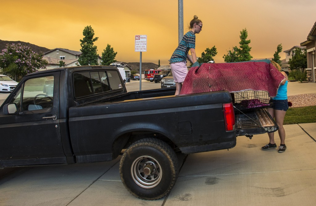 Residents along Crystal Ridge Court in Lake Elsinore, Calif., load a truck as they evacuate as the Holy Fire burns near their home on Wednesday, Aug.