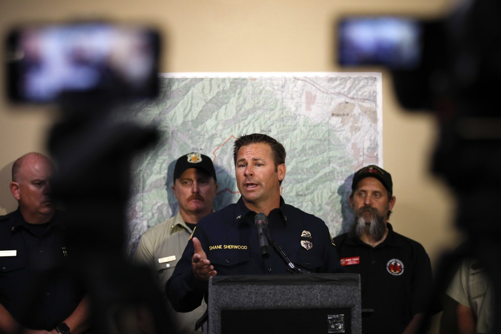 Orange County Fire Authority Battalion Chief Shane Sherwood, center, answers questions from the media during a news conference at the Orange County Fi