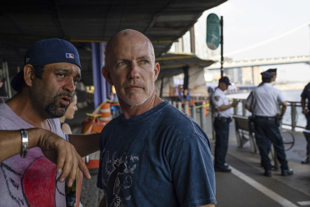 FILE - In this Aug. 5, 2018, file photo, Monte Campbell, of Stillwater, Okla., right, stands under the Brooklyn Bridge in the Manhattan borough after