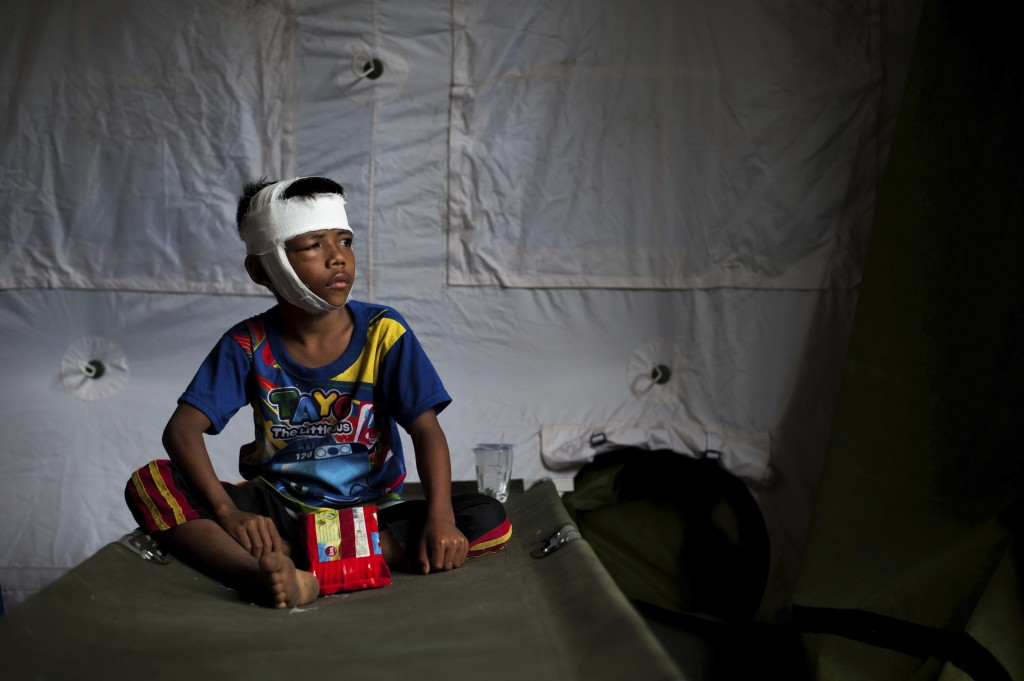 In this photo taken on Wednesday, Aug. 8, 2018, a boy who was injured in Sunday's earthquake sits on a folding bed at a makeshift hospital in Kayangan...