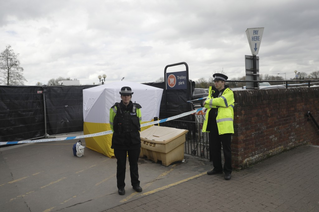 FILE - In this March 13, 2018, file photo, police officers guard a cordon around a police tent covering a supermarket car park pay machine near the sp