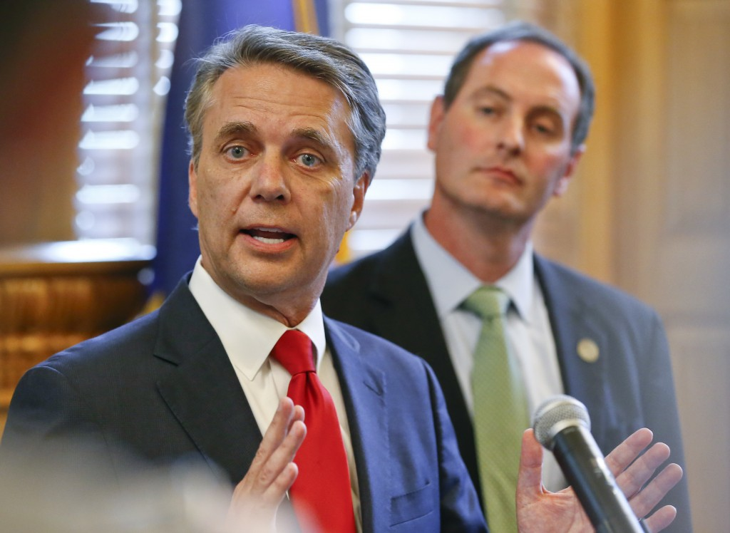 CORRECTS SPELLING OF LAST NAME TO COLYER INSTEAD OF COYLER - Kansas Gov. Jeff Colyer, left, alongside Lt. Gov. Tracey Mann, addresses the media at the