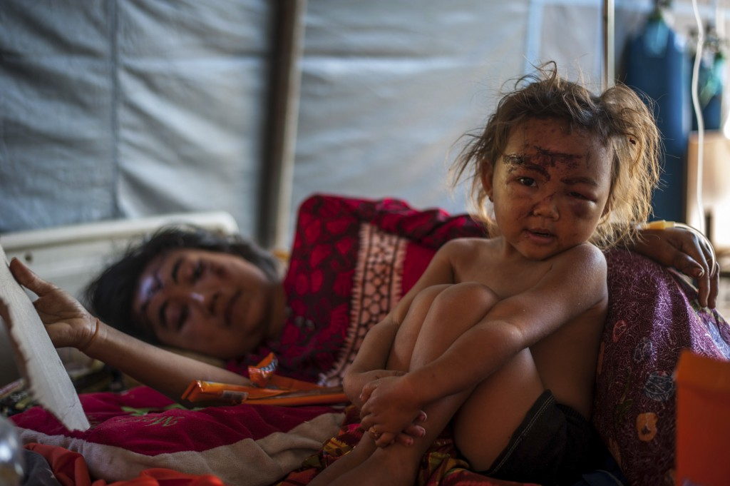 In this photo taken on Wednesday, Aug. 8, 2018, a woung girl and her mother who were injured in Sunday's earthquake rest on a bed at a makeshift hospi