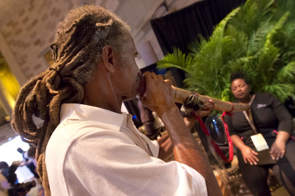 Joda Cook, from the Hippocrates Health Institute, in West Palm Beach, Fla., plays a didgeridoo as he demonstrates Vibrational Sound Healing at the ann...