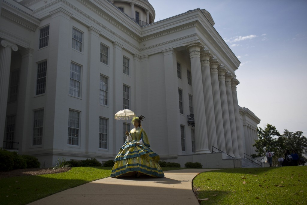 FILE - In this Monday, April 27, 2015 file photo, United Daughters of the Confederacy member Carrie McGough walks in front of the Alabama Capitol buil