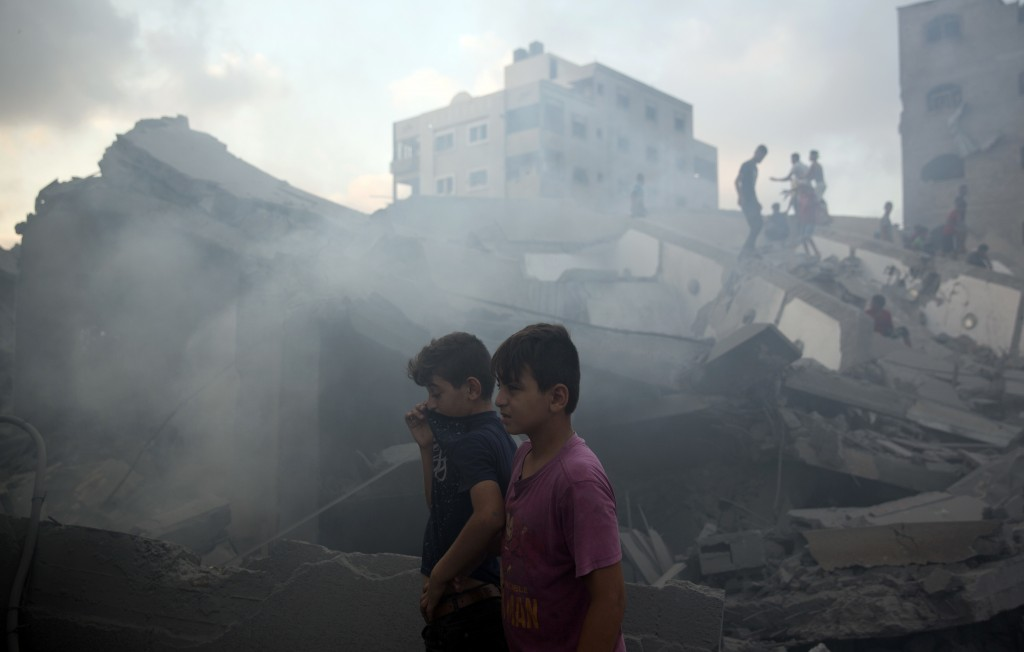 Palestinians inspect the damaged building of Said al-Mis'hal cultural center after it was hit bombed by an Israeli airstrike in Gaza City, Thursday, A