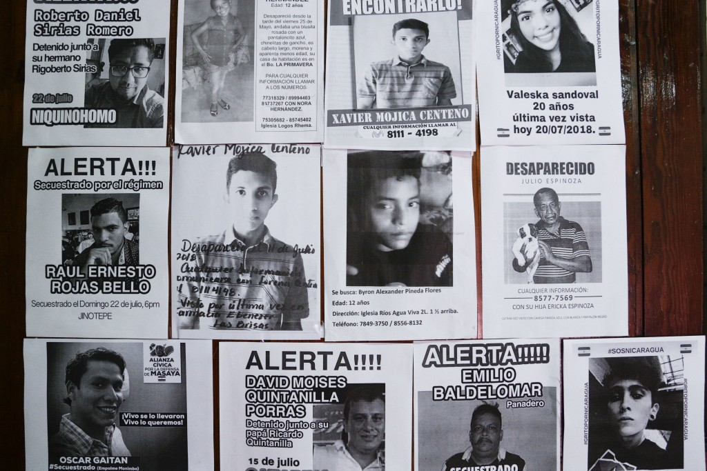 In this July 24, 2018 photo, flyers of missing persons cover a wall inside the Nicaraguan Center for Human Rights, in Managua, Nicaragua. The flyers r