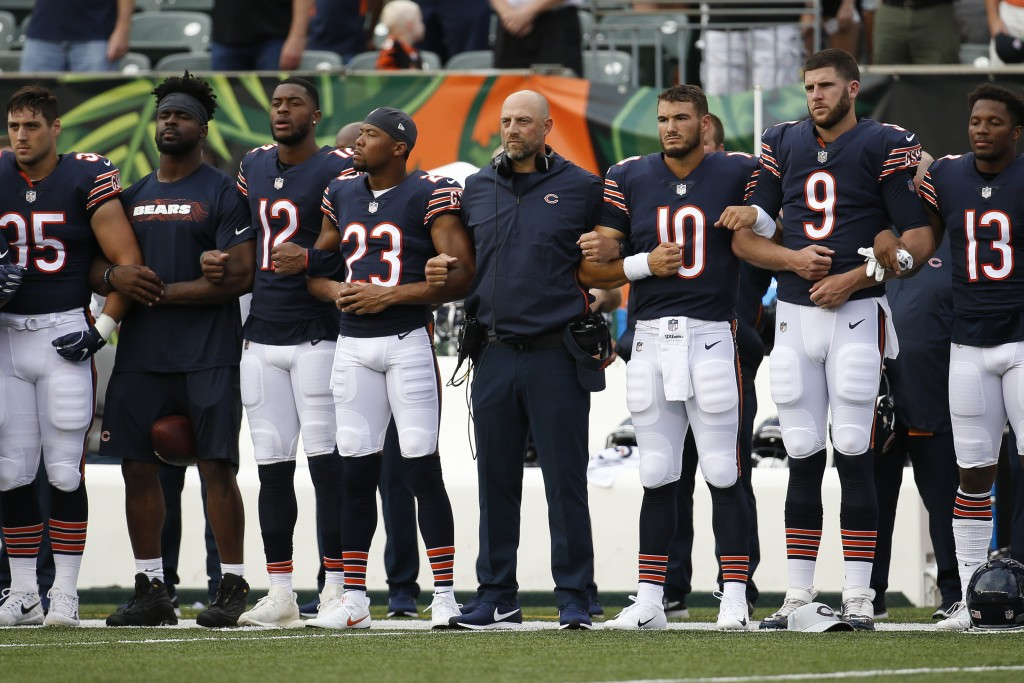 The Chicago Bears lock arms during the national anthem before the team's NFL preseason football game against the Cincinnati Bengals, Thursday, Aug. 9,