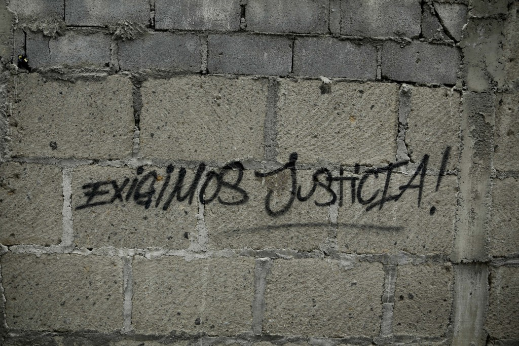 "In this July 25, 2018 photo, a graffiti that that reads in Spanish ""We demand justice"" is written on a wall outside El Chipote detention center in Man"