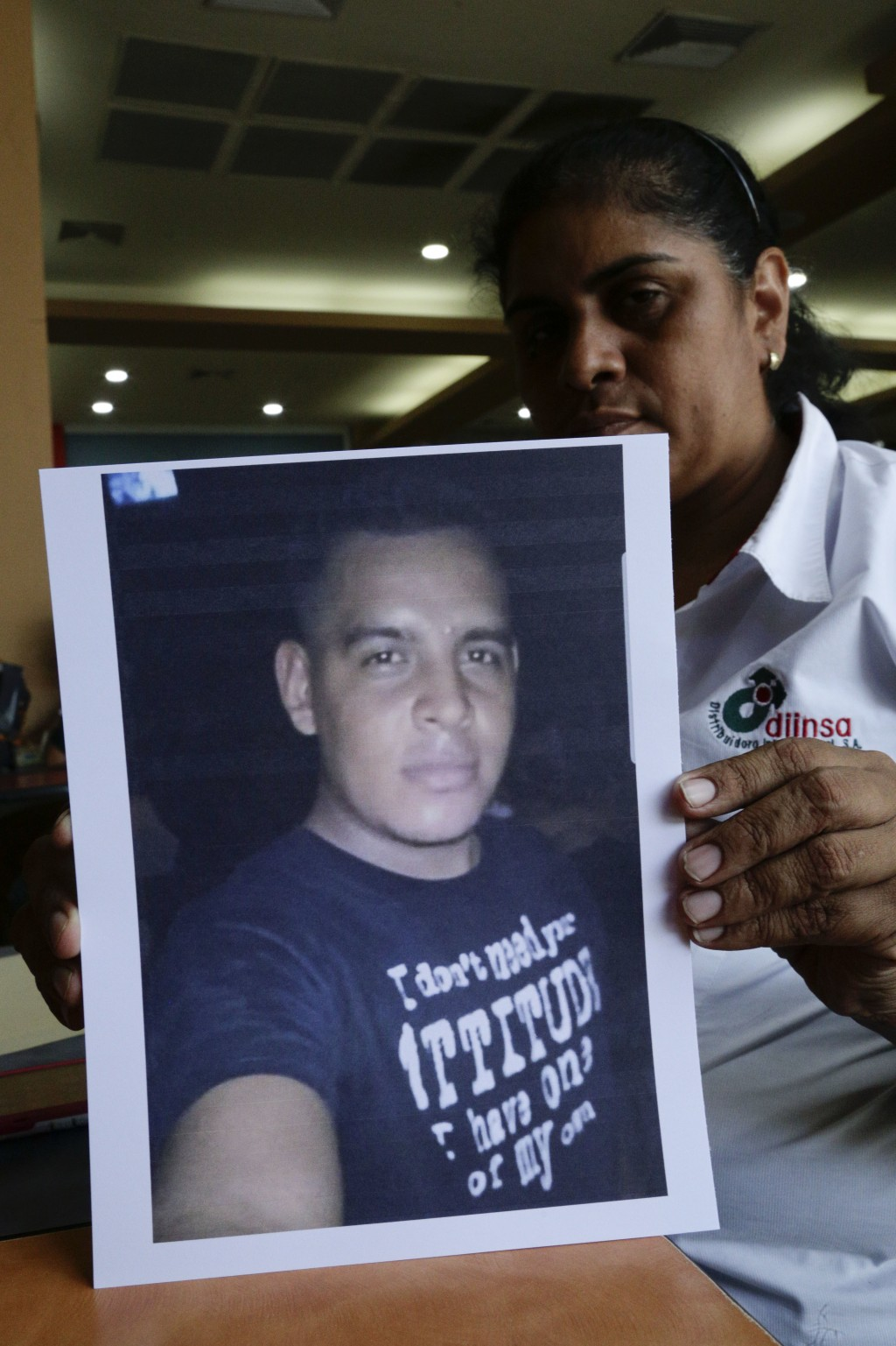 In this July 25, 2018 photo, Maria Jose Malespin shows a photograph of her missing son Lester Lenin Mayorga Malespin, who was detained at a police che