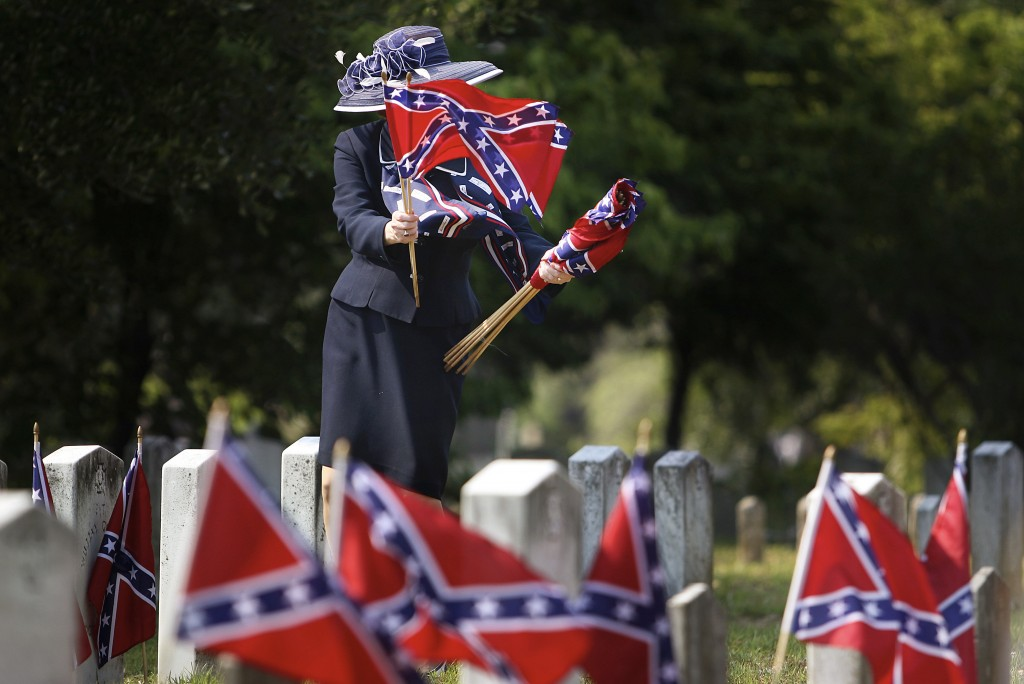 FILE - In this Tuesday, May 10, 2011 file photo, Karen Prewitt collects Confederate flags after the Confederate Memorial Day ceremony at Magnolia Ceme