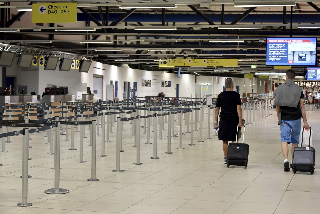 Passenger walk through the empty departure hall of the Schoenefeld airport near Berlin Friday, Aug. 10, 2018 when several flights of Irish Ryanair air