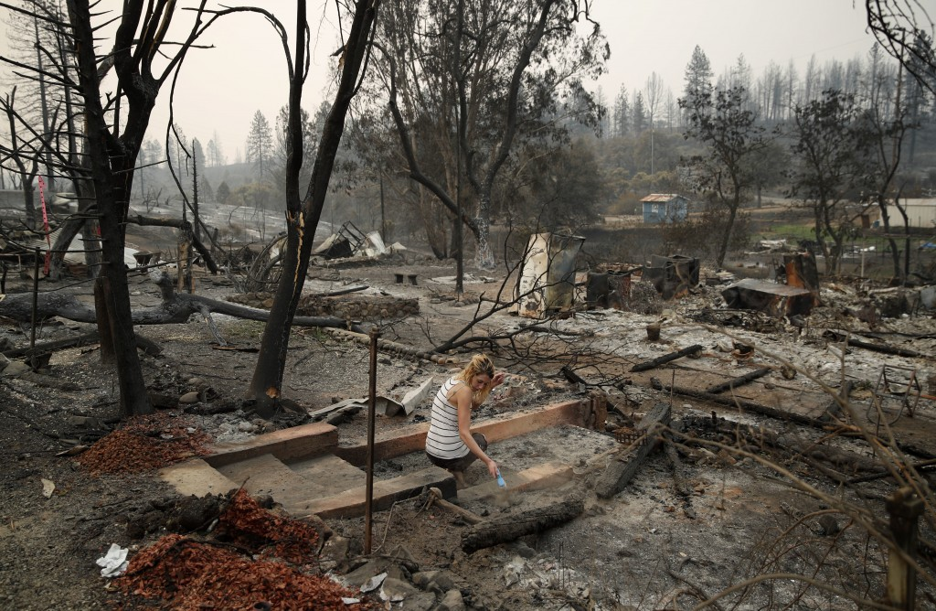 Bree Seville uses a small brush to sweep the stairs leading to burned out ruins of her fiancee's mother's home in the Keswick area of Redding, Calif.,