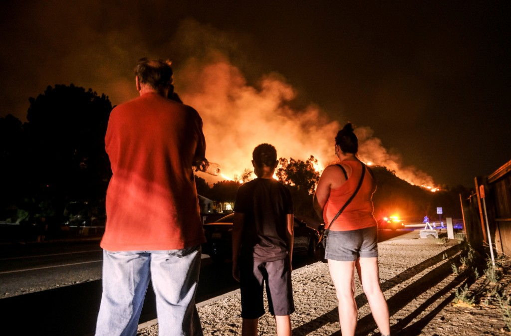 Residents watch the Holy Fire burning in the Cleveland National Forest in Lake Elsinore, Calif., Thursday, Aug. 9, 2018. (AP Photo/Ringo H.W. Chiu)