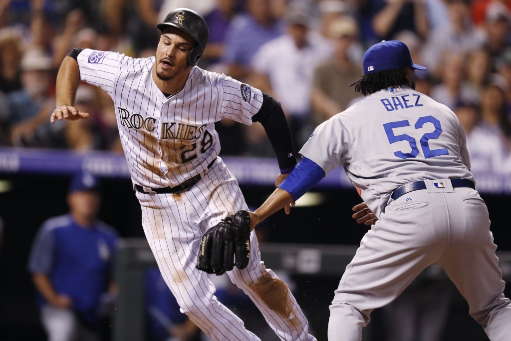 Colorado Rockies' Nolan Arenado, left, stumbles past Los Angeles Dodgers relief pitcher Pedro Baez after Armando scored on a passed ball in the sevent