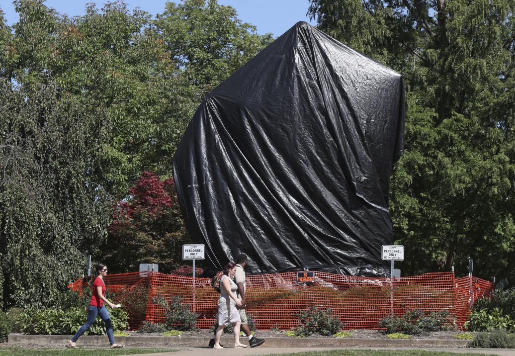 FILE - In this Tuesday, Sept. 19, 2017 file photo, a fence with no trespassing signs has been installed around a covered statue of confederate Gen. Ro
