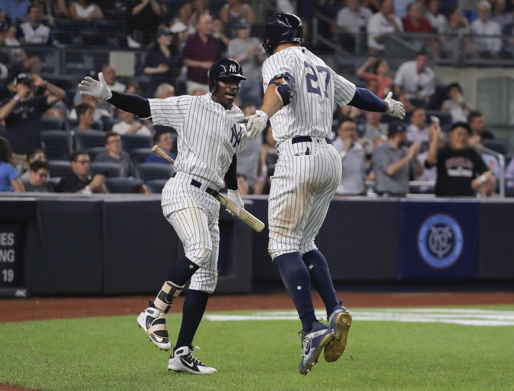 New York Yankees' Didi Gregorius, left, and Giancarlo Stanton (27) celebrate after Stanton hit a solo home run against the Texas Rangers during the fi