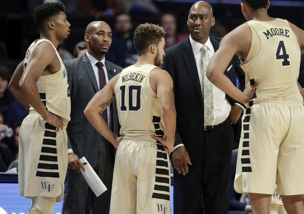 This photo from Nov. 28, 2017, shows Wake Forest assistant coach Jamill Jones, second from left, with the team and head coach Danny Manning, second fr