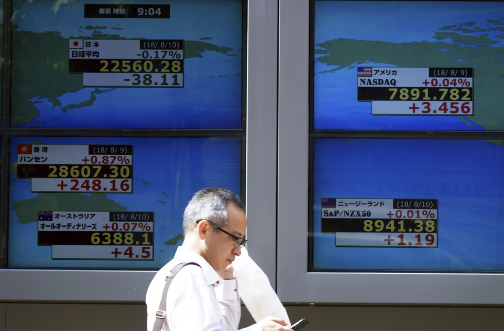 A man walks past an electronic stock board showing Japan's Nikkei 225 index and lather coin try's index at a securities firm in Tokyo Friday, Aug. 10,