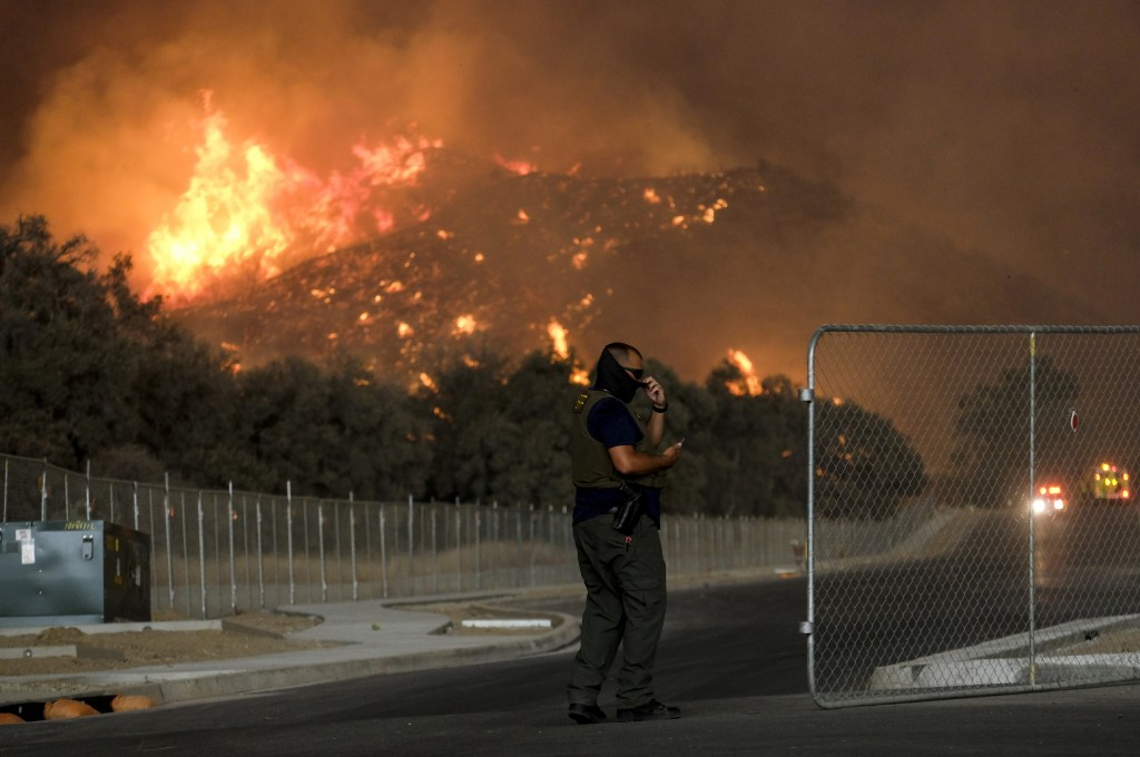 A sheriff's deputy stands guard at a gate near a hillside as the Holy Fire burns in the Cleveland National Forest at Temescal Valley in Corona, Calif.