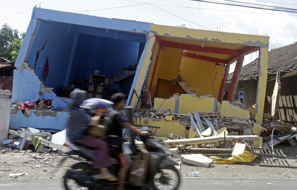 A motorcycle passes buildings destroyed by Sunday's earthquake in North Lombok, Indonesia, Friday, Aug. 10, 2018. The north of Lombok was devastated b
