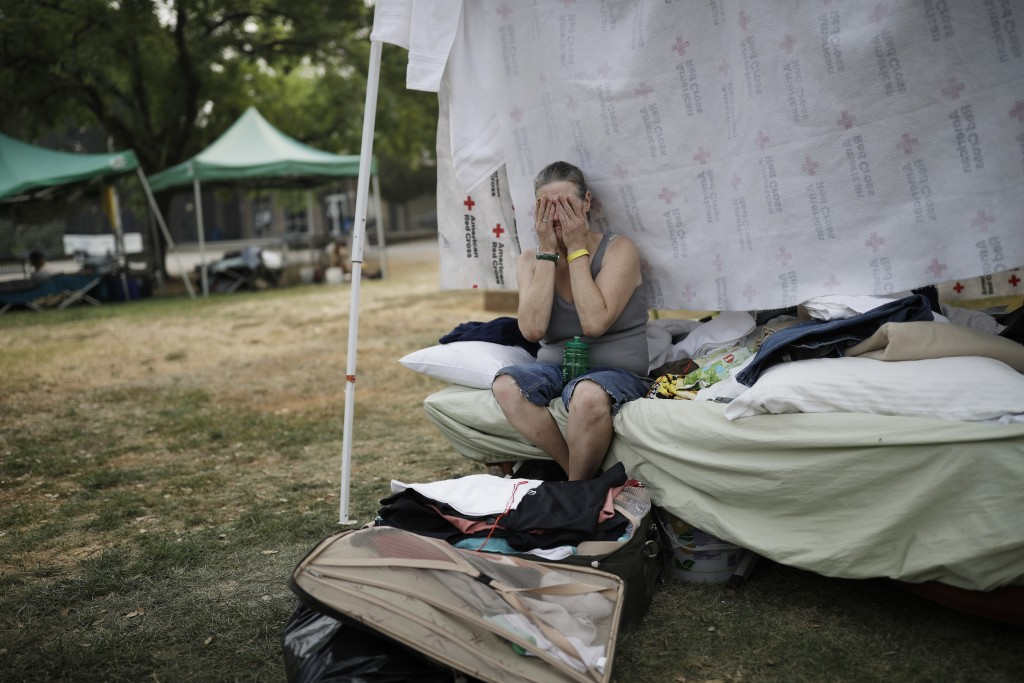Starla Davis cries as she packs a suitcase in her makeshift tent at an evacuation center Thursday, Aug. 9, 2018, in Redding, Calif. Davis was living w