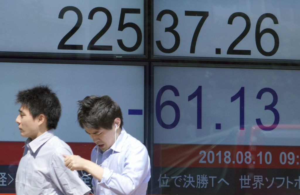 Men walk past an electronic stock board showing Japan's Nikkei 225 index at a securities firm in Tokyo Friday, Aug. 10, 2018. Shares were lower in Asi