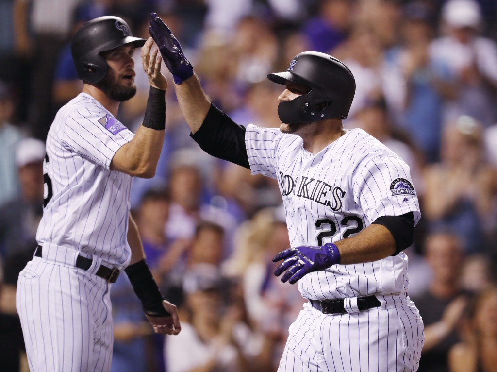 Colorado Rockies' David Dahl, left, congratulates Chris Iannetta as he crosses home plate after hitting a three-run home run off Los Angeles Dodgers r