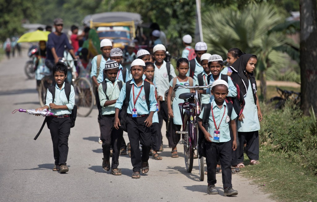In this Thursday, Aug. 9, 2018 photo, school children walk on a road in Mayong, 45 kilometers (28 miles) east Gauhati, India. A draft list of citizens