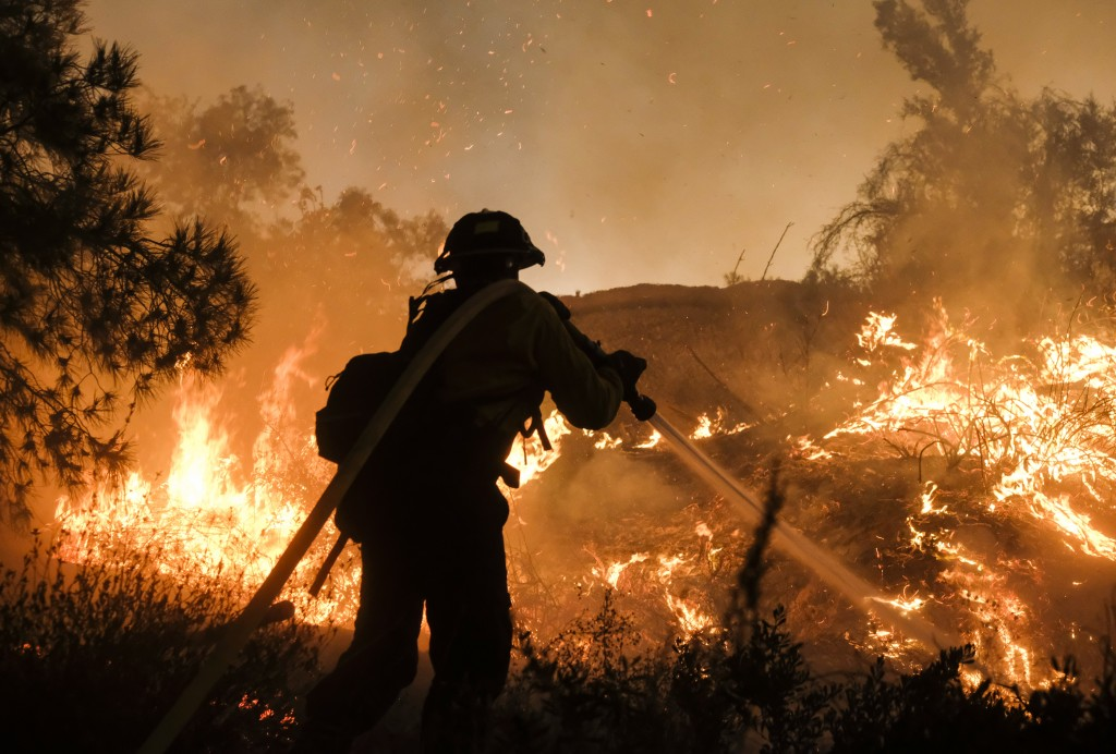 A firefighter battles the Holy Fire burning in the Cleveland National Forest along a hillside at Temescal Valley in Corona, Calif., Thursday, Aug. 9,