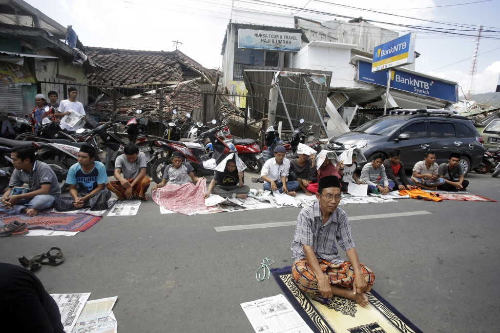 Villagers attend Muslim Friday prayer in front of the damage buildings in North Lombok, Indonesia, Friday, Aug. 10, 2018. The north of Lombok was deva...