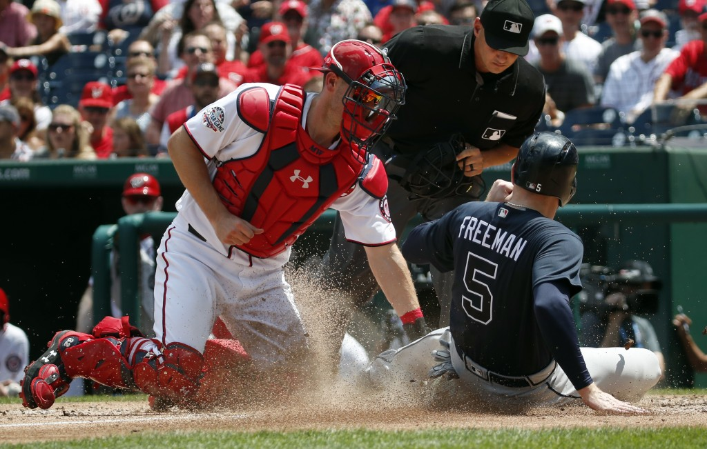 Washington Nationals catcher Matt Wieters makes the tag at home plate on Atlanta Braves' Freddie Freeman as home plate umpire Vic Carapazza prepares t