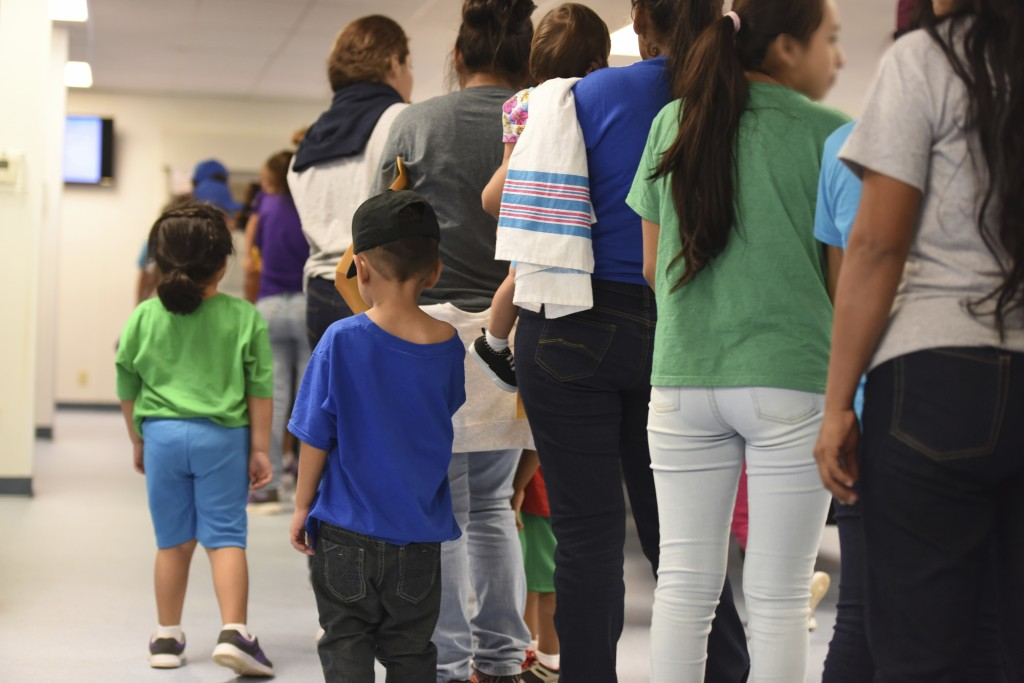 In this Thursday, Aug. 9, 2018, photo, provided by U.S. Immigration and Customs Enforcement, mothers and their children stand in line at South Texas F