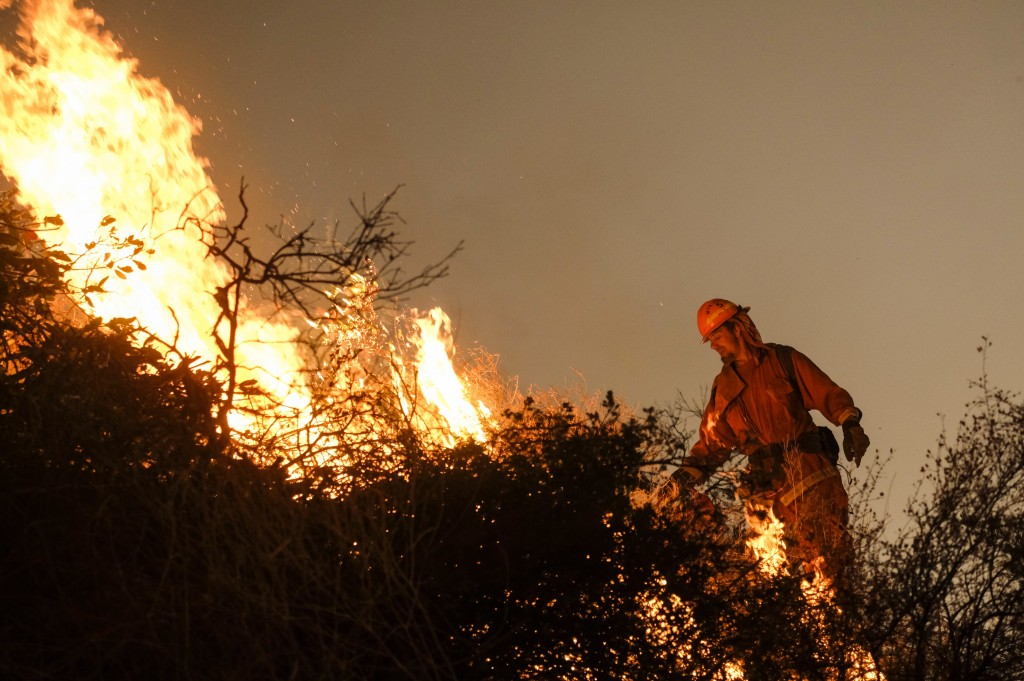 A firefighter sets a backburn to fight the Holy Fire as it burns in the Cleveland National Forest along a hillside at Temescal Valley in Corona, Calif