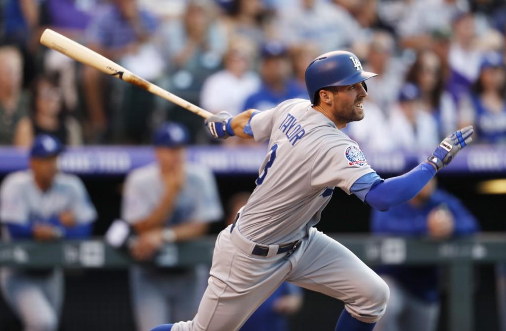 Los Angeles Dodgers' Chris Taylor follows the flight of his sacrifice fly to bring in a runner off Colorado Rockies starting pitcher Tyler Anderson in